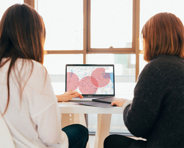 Two women reviewing a radius map